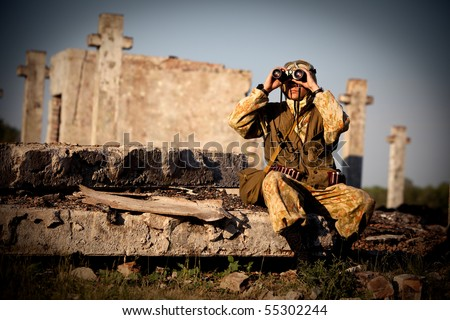 Man in camouflage uniform is looking through the binoculars. Urban ruins on the background. - stock photo