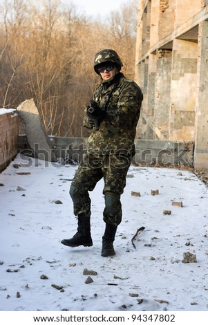 Man in camouflage with rifle in his hands - stock photo