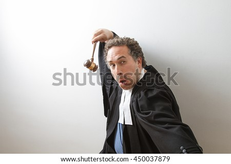 Man in canadian lawyer robe with a gavel in hand in fake kung fu fighting form - stock photo