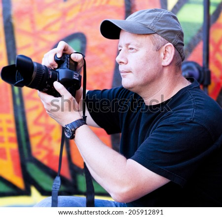 Man in cap taking photos with graffiti background - stock photo