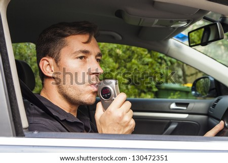 Man in car blowing into breathalyzer with 0 reading. - stock photo
