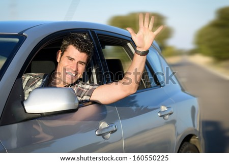 Man in car driving and waving. Male driver having fun traveling on road trip. - stock photo