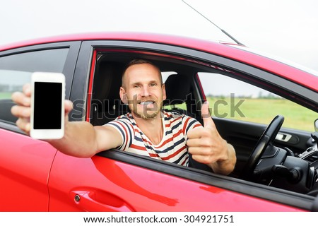 Man in car showing smart phone display and showing thumb up. Focus on model. - stock photo