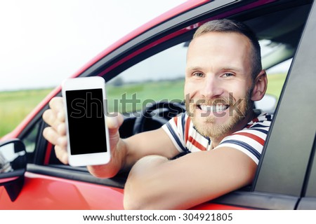 Man in car showing smart phone display smiling happy. Focus on model. Toned photo. - stock photo