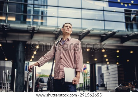 Man in casual clothes holding laptop and posing on modern street. - stock photo