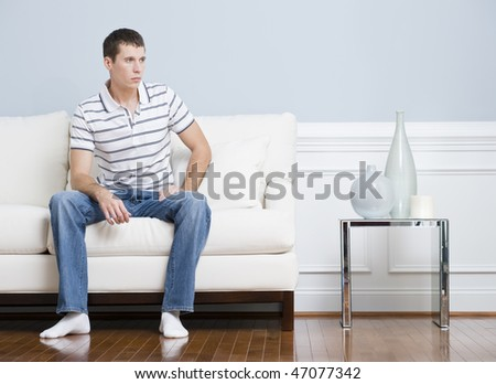 Man in casual clothing sitting on a white couch in a living room. He has a blank expression and is looking to the side. Horizontal format. - stock photo