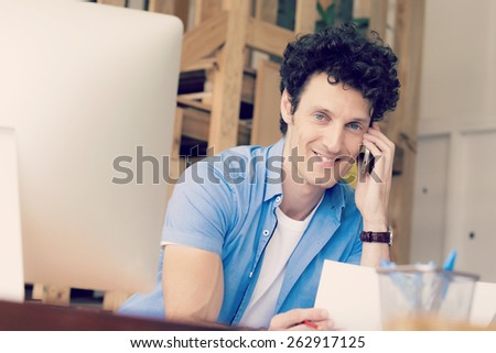 Man in casual wear with his mobile in office