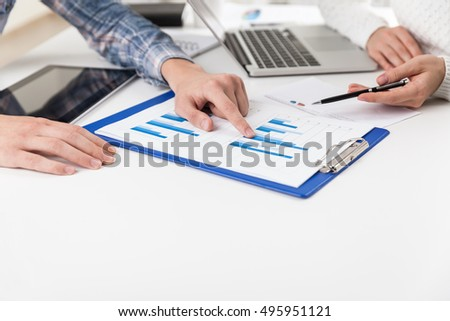 Man in checkered shirt is showing graph to his colleague. Close up of hands with pen and clippad. Concept of stats