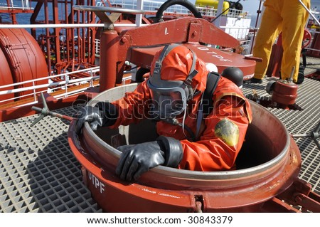 man in chemical suit entering inside  cargo tank on chemical ship for cleaning operation - stock photo