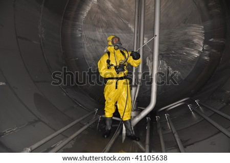 man in chemical suit inside of cargo tank on chemical tanker for cleaning operation - stock photo