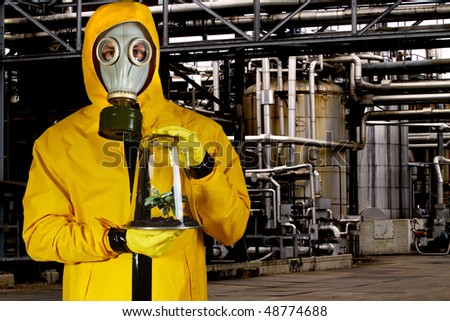 Man in chemical suit with mask holding plant in a portable greenhouse at chemical plant - stock photo