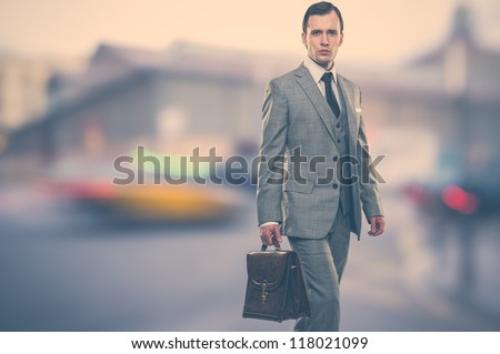 Man in classic grey suit with briefcase  outdoors - stock photo