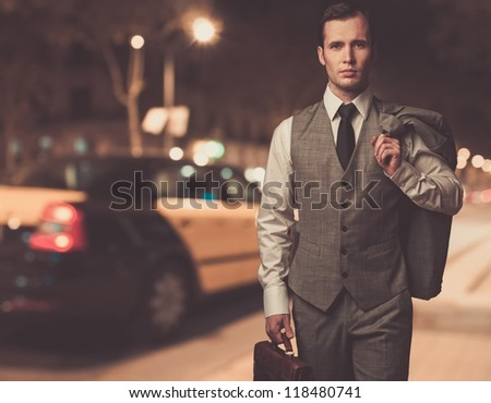 Man in classic grey suit with briefcase walking outdoors at night - stock photo