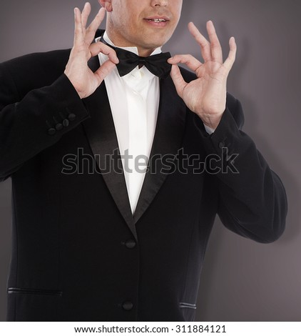 Man in classic tuxedo on abstract dark grey background. - stock photo