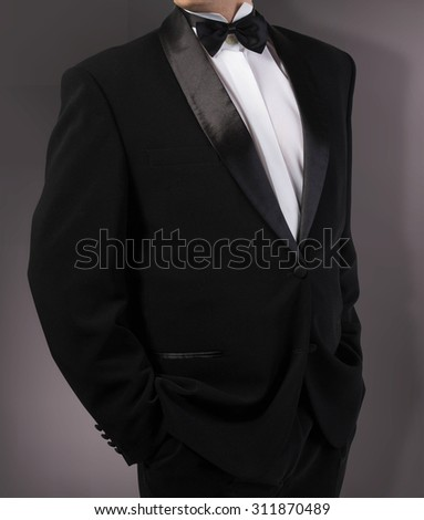 Man in classic tuxedo on abstract dark grey background.photography studio - stock photo