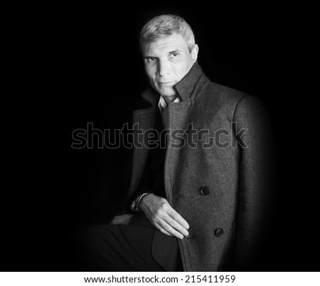 Man in coat at the age of forty-six years on black  background - stock photo