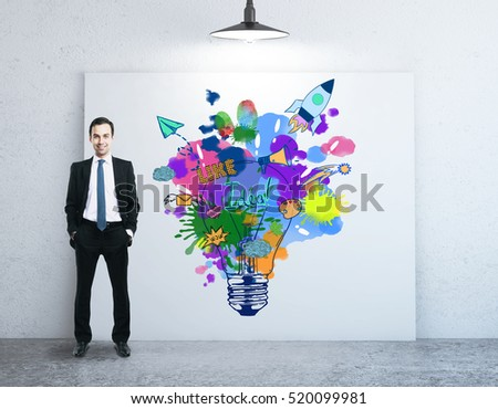 Man in concrete room with colorful light bulb on billboard. Creative idea concept
