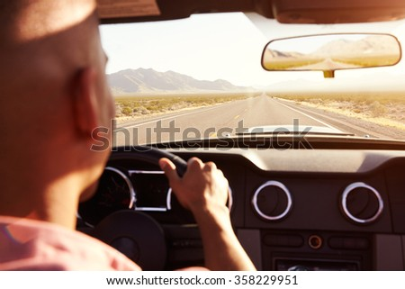 Man In Convertible Car Driving Along Open Road - stock photo