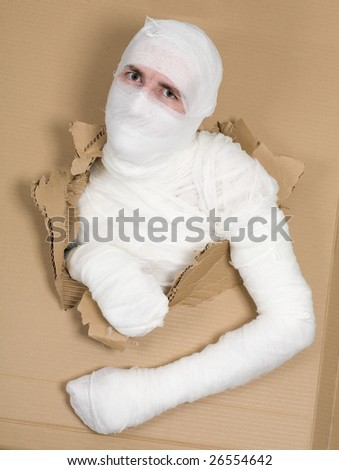 Man in costume mummy looking through hole in cardboard - stock photo
