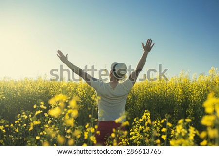 Man in country in summer day in yellow flowers