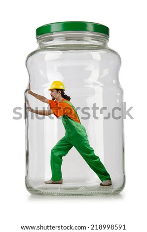 Man in coveralls imprisoned in glass jar - stock photo