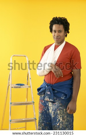 Man in Coveralls Wearing Sling - stock photo