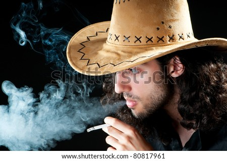 Man in cowbow hat smoking - stock photo