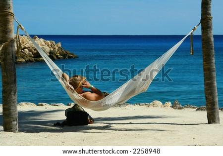 Man in cowboy hat in hammock talking on a cellphone. - stock photo