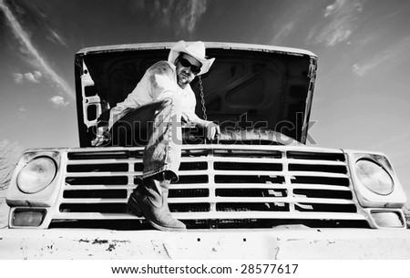 Man in cowboy hat under the hood of truck - stock photo