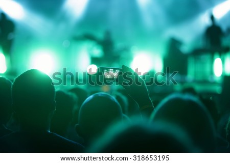 man in crowed with smart phone recording concert  - stock photo