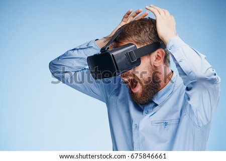 Man in 3d glasses, playing games on a blue background