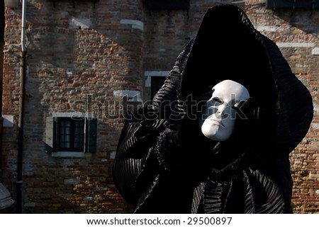 Man in dark halloween like costume on streets of Venice during carnival