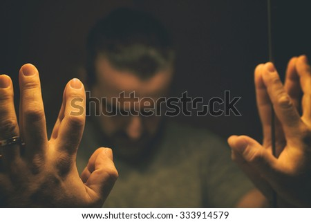 Man in despair with raised hands and bowed hand, in a low light room looking in front of mirror - stock photo