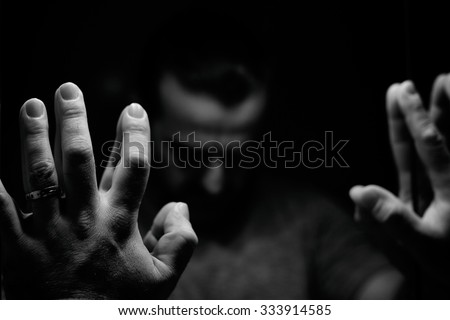 Man in despair with raised hands and bowed hand, monochromatic image in a low light room looking in front of mirror - stock photo