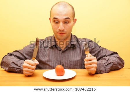 Man in diet trying to eat a healthy tomato