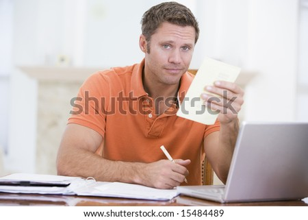 Man in dining room with laptop holding paperwork - stock photo