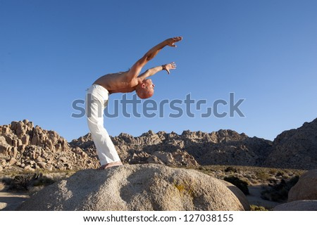 Man in ecstatic yoga backbend outdoors in the desert. - stock photo