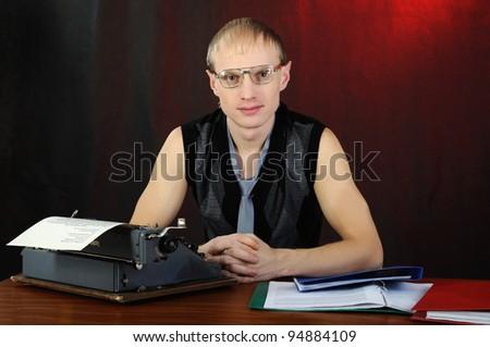 Man in eyeglasses with old typewriter. - stock photo