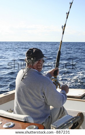 Man in Fighting Chair Reeling in Gamefish - stock photo