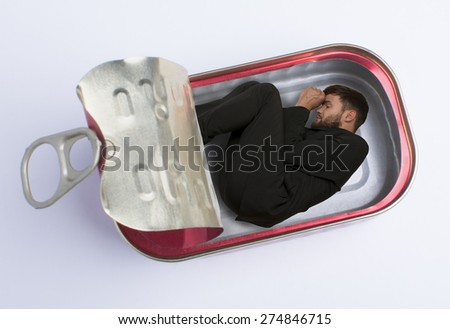 Man in fish can, Studio Shot, montage - stock photo