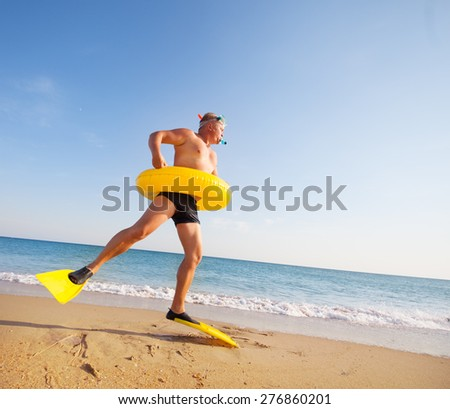 man in flippers and mask on the bank of the sea - stock photo