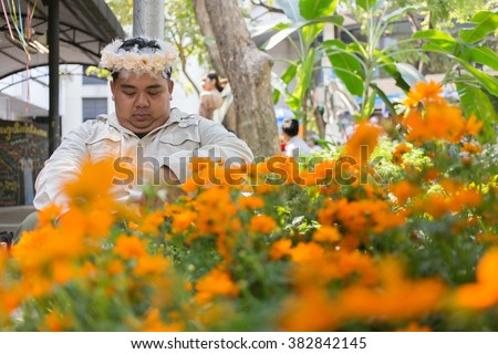 Man in flower wreath. man with wreath of flowers. Man wearing flowers crown and sit behind the orange color flowers field. Selective focus at man. - stock photo