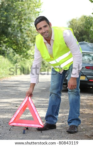 Man in fluorescent vest putting out a warning triangle by a breakdown - stock photo