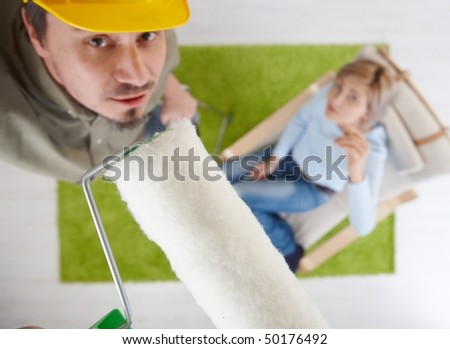 Man in focus standing on ladder using paint roller, woman in background sitting in armchair, looking up. Overhead shot  focus placed on roller. - stock photo