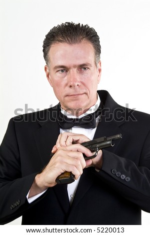 Man in formal attire, cocking a 9mm automatic weapon, taken in front a white background. - stock photo