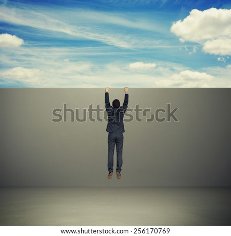 man in formal wear climbing up on grey wall - stock photo