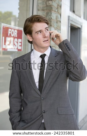 """man in front of a store with a """"for lease"""" sign on the phone - stock photo"""