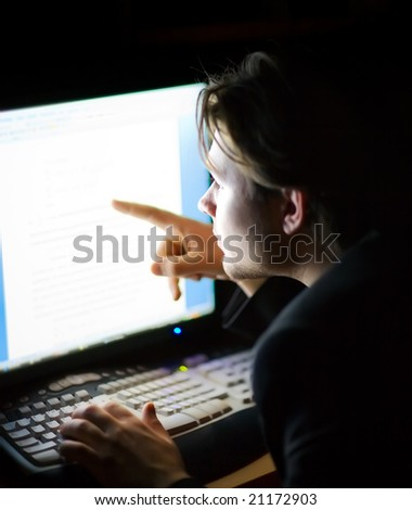 Man in front of computer screen. Dark night room. - stock photo