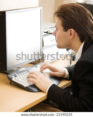 Man in front of computer screen. Shallow dof focus on keyboard. - stock photo