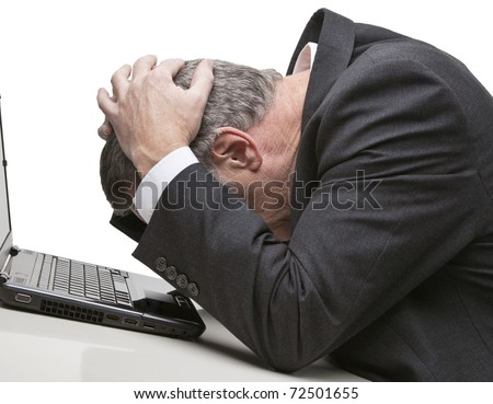 man in front of computer with head in his hands against a white background - stock photo